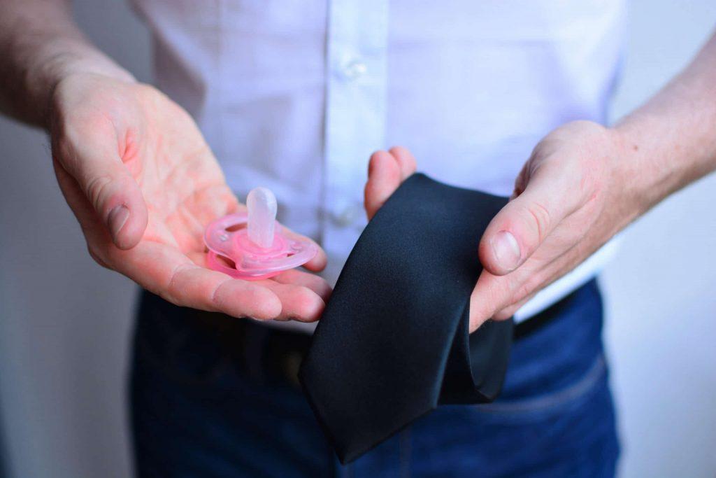 Zwei Hände, eine mit Schnuller, die andere mit Krawatte © asbe24 Adobe Stock Photo