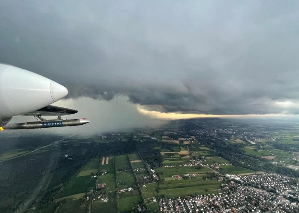 Der Silberjodid-Generator läuft. Das Bild wurde während eines Einsatzes am 25. Juli 2021 aufgenommen. Unten dem Flugzeug sieht man den südlichen Rand von Kolbermoor, im Hintergrund die Stadt Bad Aibling.